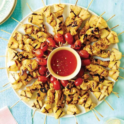 Chicken skewers arranged in a circle around dipping sauce