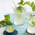 fresh mint limeade in clear glasses on blue towel with straws