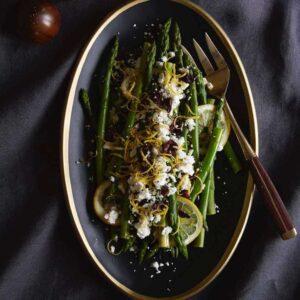 lemon asparagus on black plate with olives