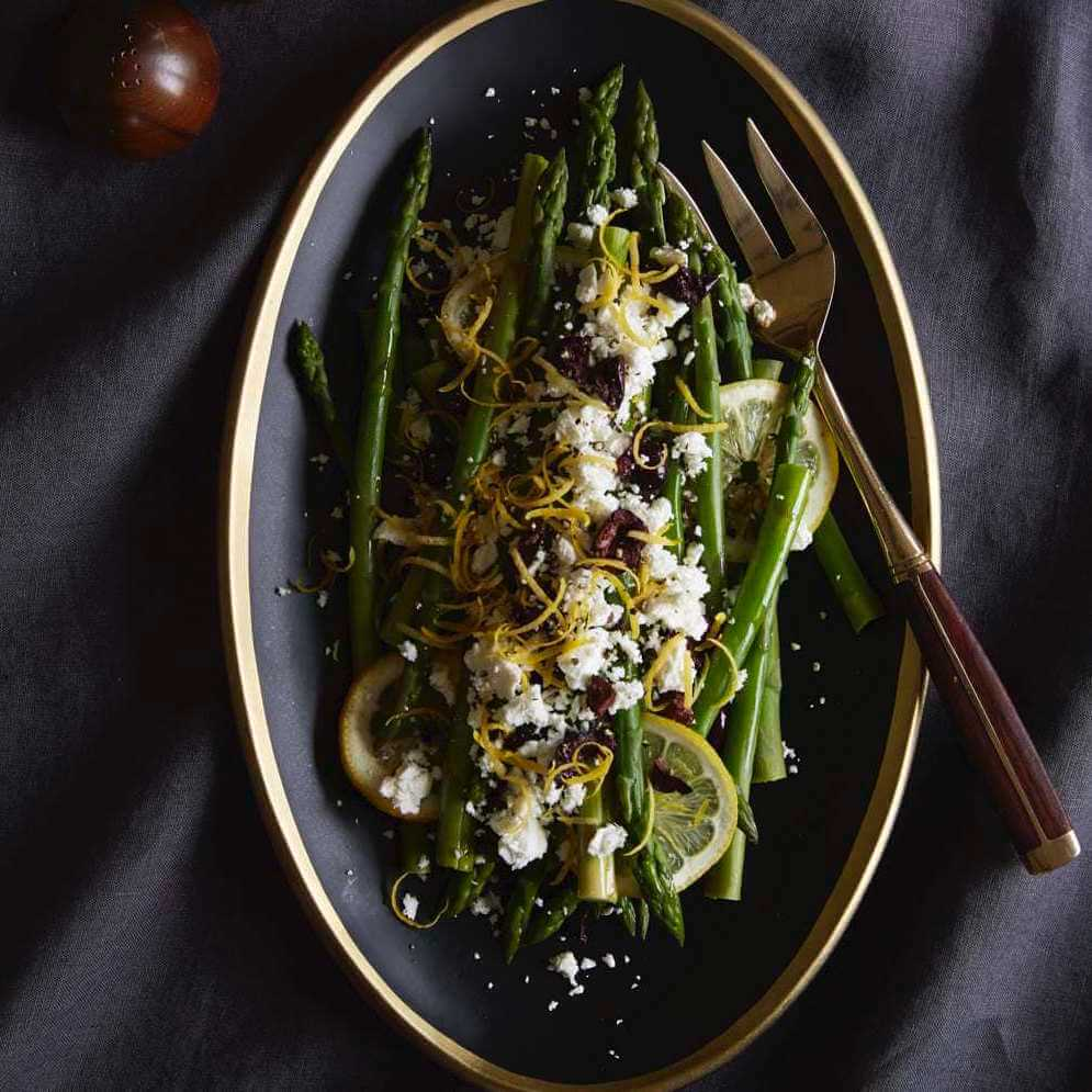 lemon asparagus on black plate with olives
