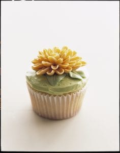 Cupcake decorated with yellow Mum made from buttercream frosting