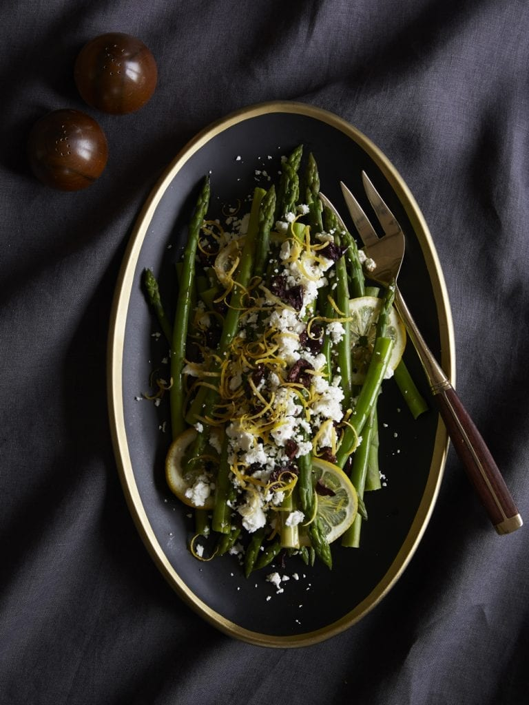 Asparagus with Lemon, Olives and Feta in bowl on dark background