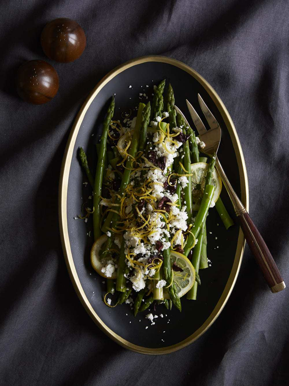 Asparagus with Lemon, Olives and Feta on charcoal plate with bronze fork