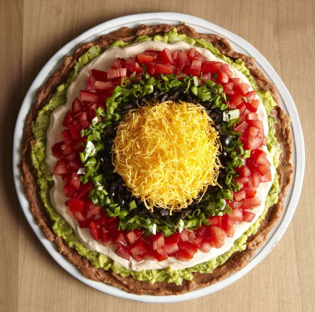 seven layer mexican dip on a round white platter