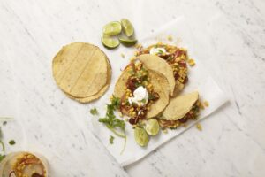 Corn Chorizo Tacos displayed on parchment with extra corn tortillas and limes