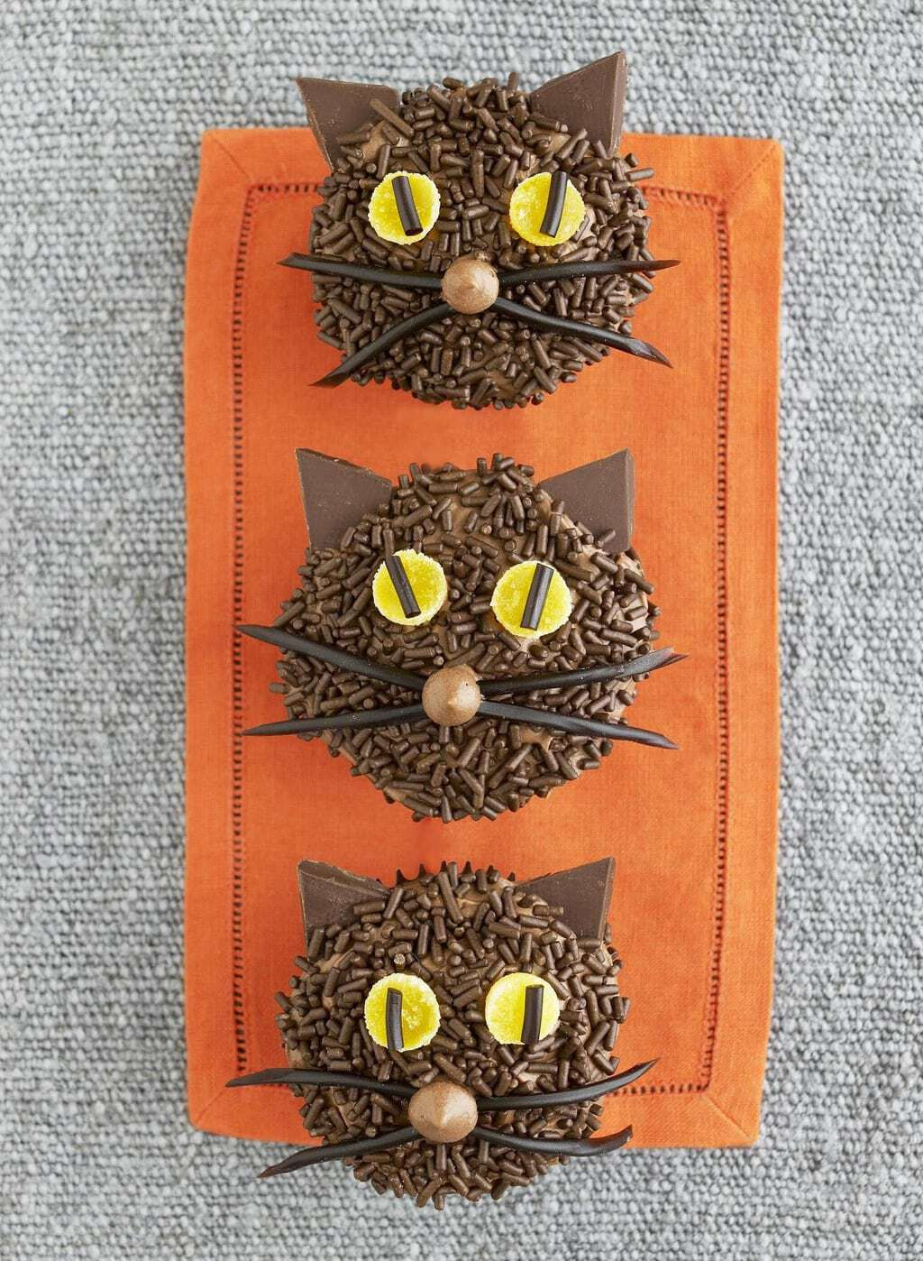 Chocolate Black Cat Cupcakes with orange cloth background
