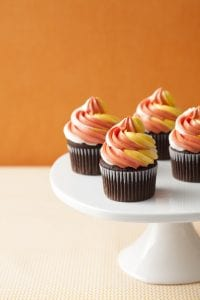 Four chocolate cupcakes frosted with orange yellow and white buttermilk frosting