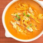 Close up image of Chicken Tomato Bisque on orange background