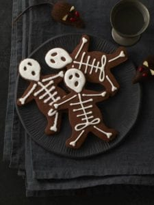 Skeleton cookies on dark plate, napkins and surface