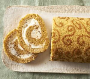 Slices of Pumpkin Roll Cake on tan platter