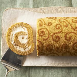 Slice of Pumpkin Cake Roll on tan platter