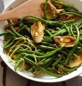 Green beans with capers and artichokes in pan