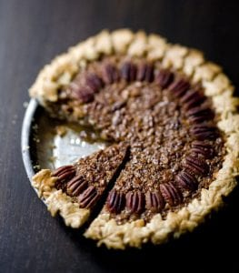 Gingered Coconut Pecan Pie sliced and on dark surface