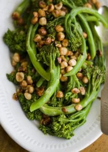 Broccoli with peanuts on white platter