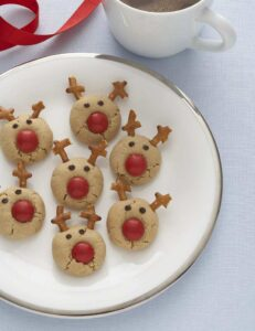 reindeer cookies with red noses on white holiday plate