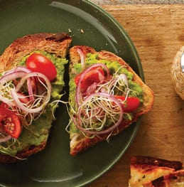 Avocado Toasts with Sprouts on olive green plate