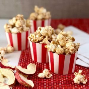 Apple cinnamon popcorn in red and white cups with dried apples