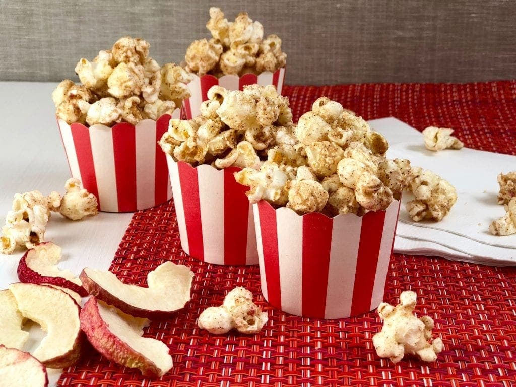 Apple cinnamon popcorn in red and white cups on red placemat