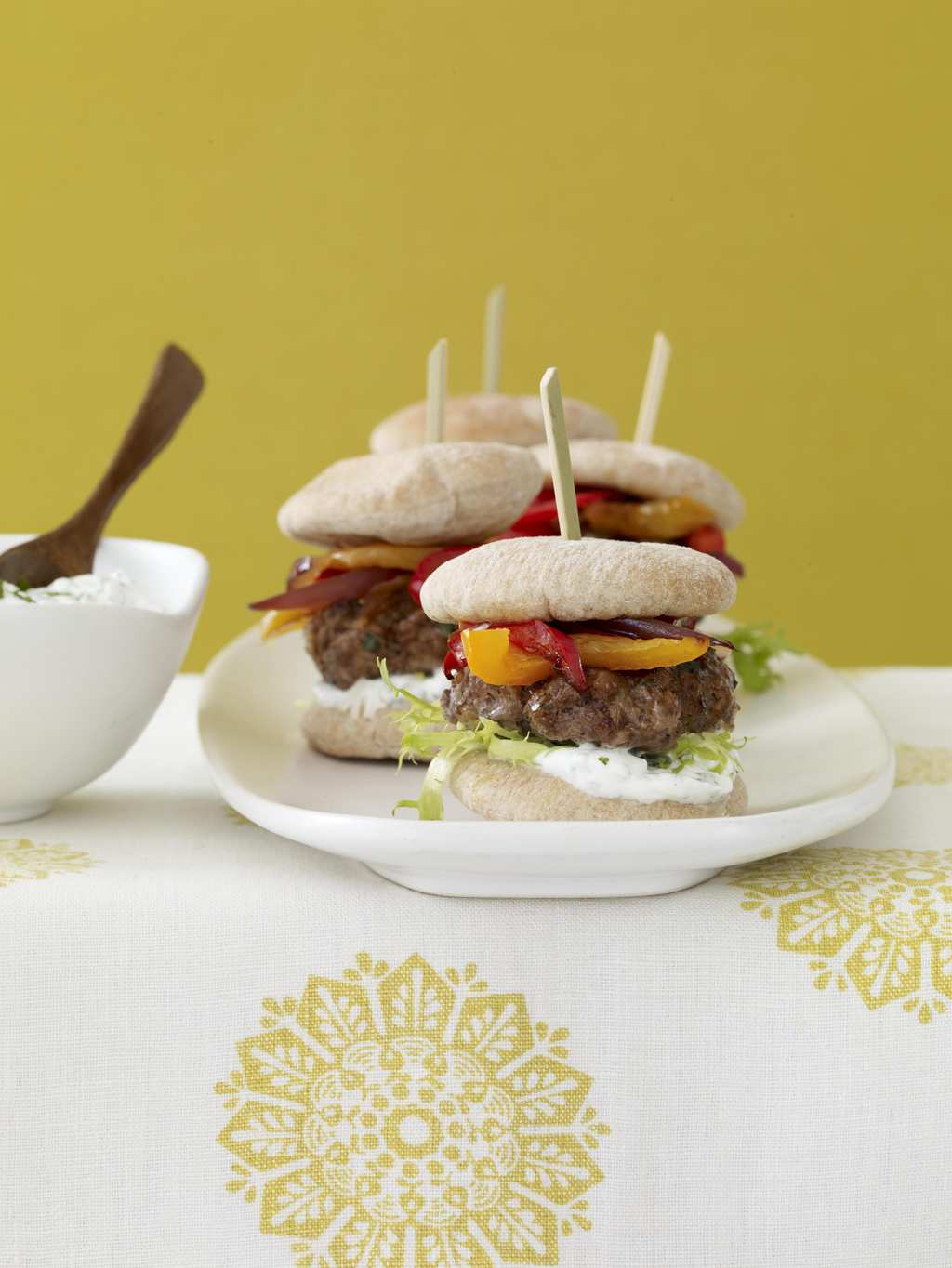 Mini burgers on white platter w yellow linen and background
