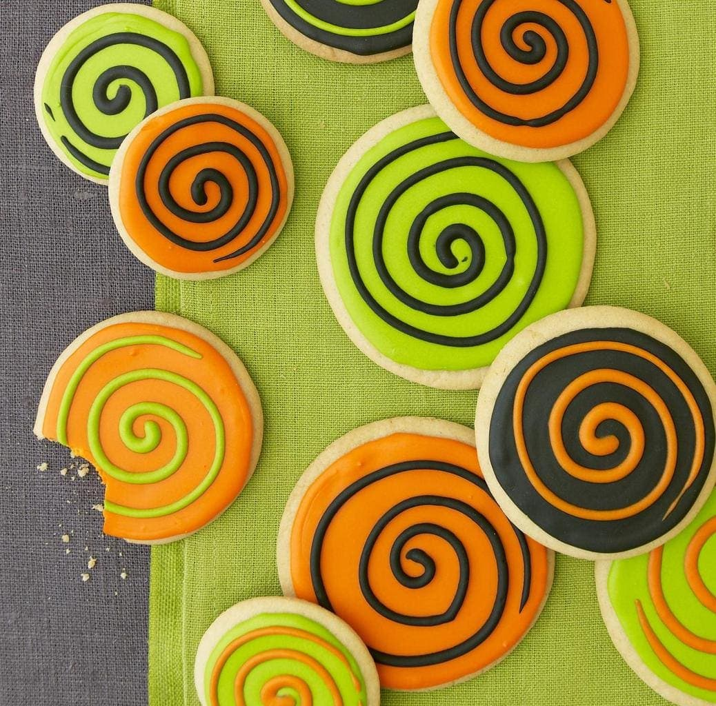 Spooky Spiral Cookies with a bite taken out of one, sitting on a green cloth