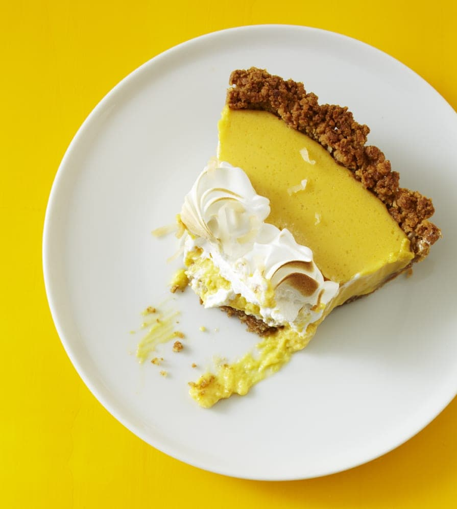 Overhead view of a slice of coconut mango custard pie on a white pate. A generous bite has already been taken from the slice.