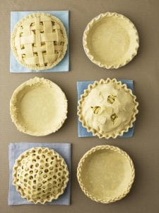 6 beautiful pie crust examples on tan surface