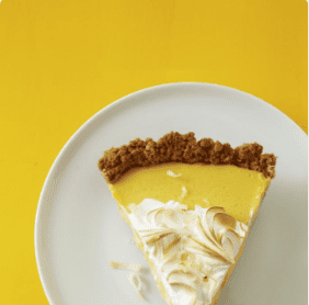 blow your mind coconut mango pie on white plate with yellow background