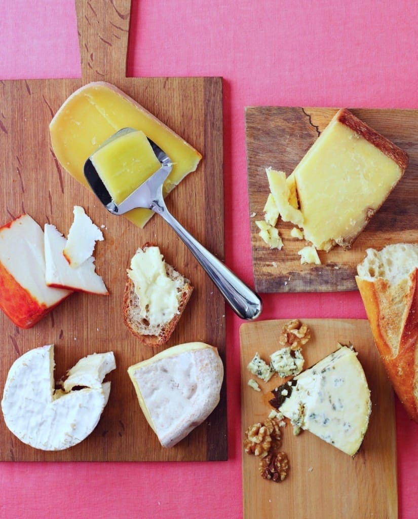 Cheeses on boards and pink background
