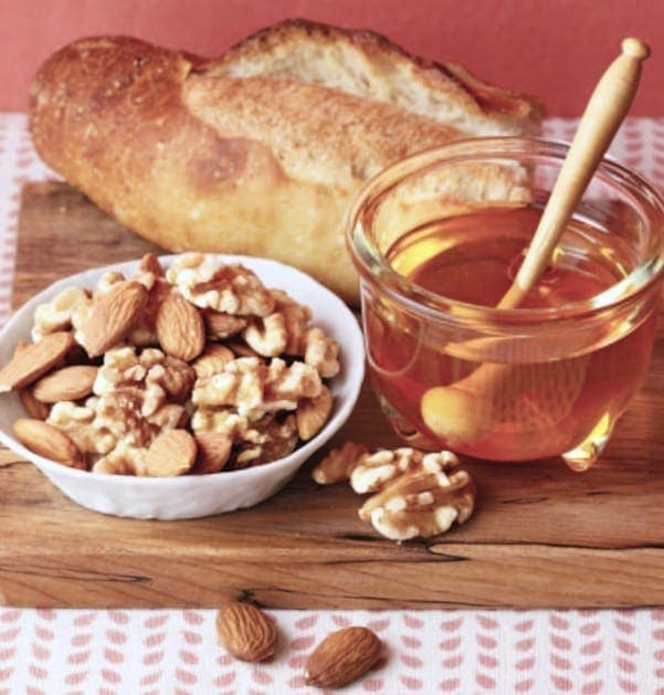 Bread nuts and honey on board w pink background
