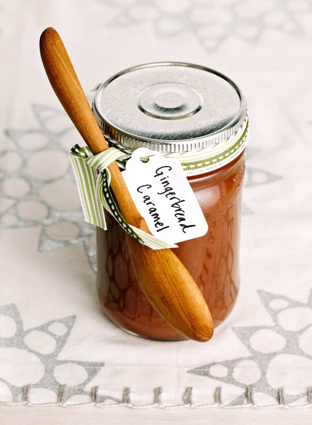 Gingerbread Caramel Sauce in a jar with a wooden spoon