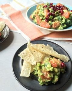 Spicy guacamole with grapefruit served on a plate with taco chips