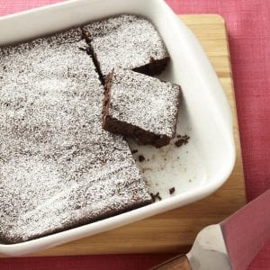 Close up recipe image of brownies dusted with powdered sugar
