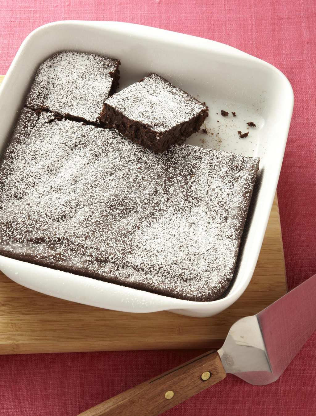 Fudgy Squash Brownies are baked in a square pan and dusted with confectioners' sugar