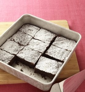 Brownies dusted with powdered sugar in white baking dish