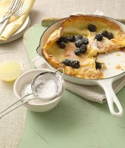 Danish Puffcake with fresh berries and powdered sugar in pan