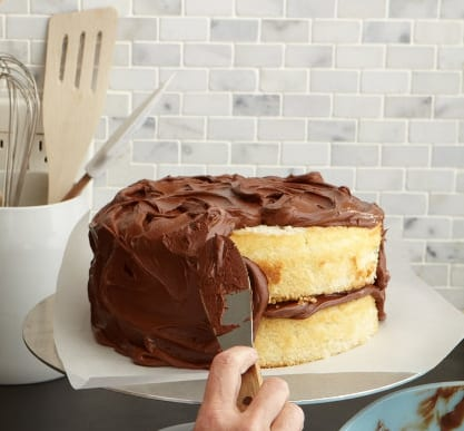 Classic yellow cake with chocolate frosting on white cake plate - process is cake being frosted
