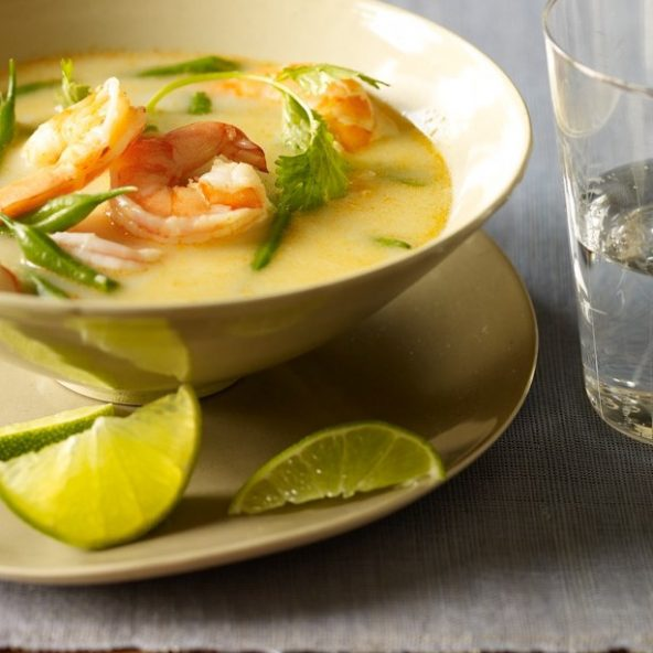 Thai coconut shrimp soup in a bowl with limes