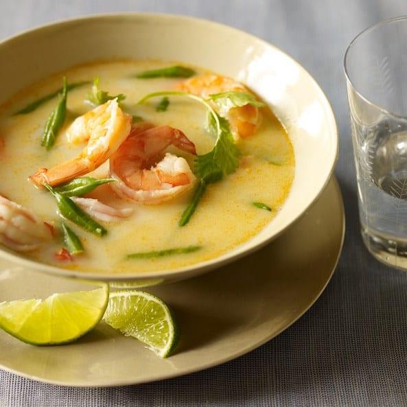 thai coconut shrimp soup in cream colored bowl w lime