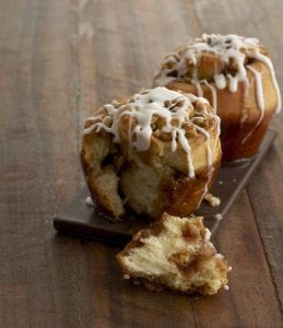 Two Maple Walnut Sticky Buns on brown tile