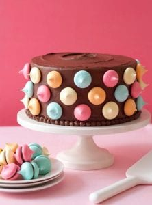 Rich chocolate frosting and meringue kisses cover a cake