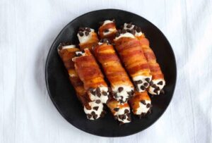 Pile of Bacon Wrapped Cannoli on dark plate