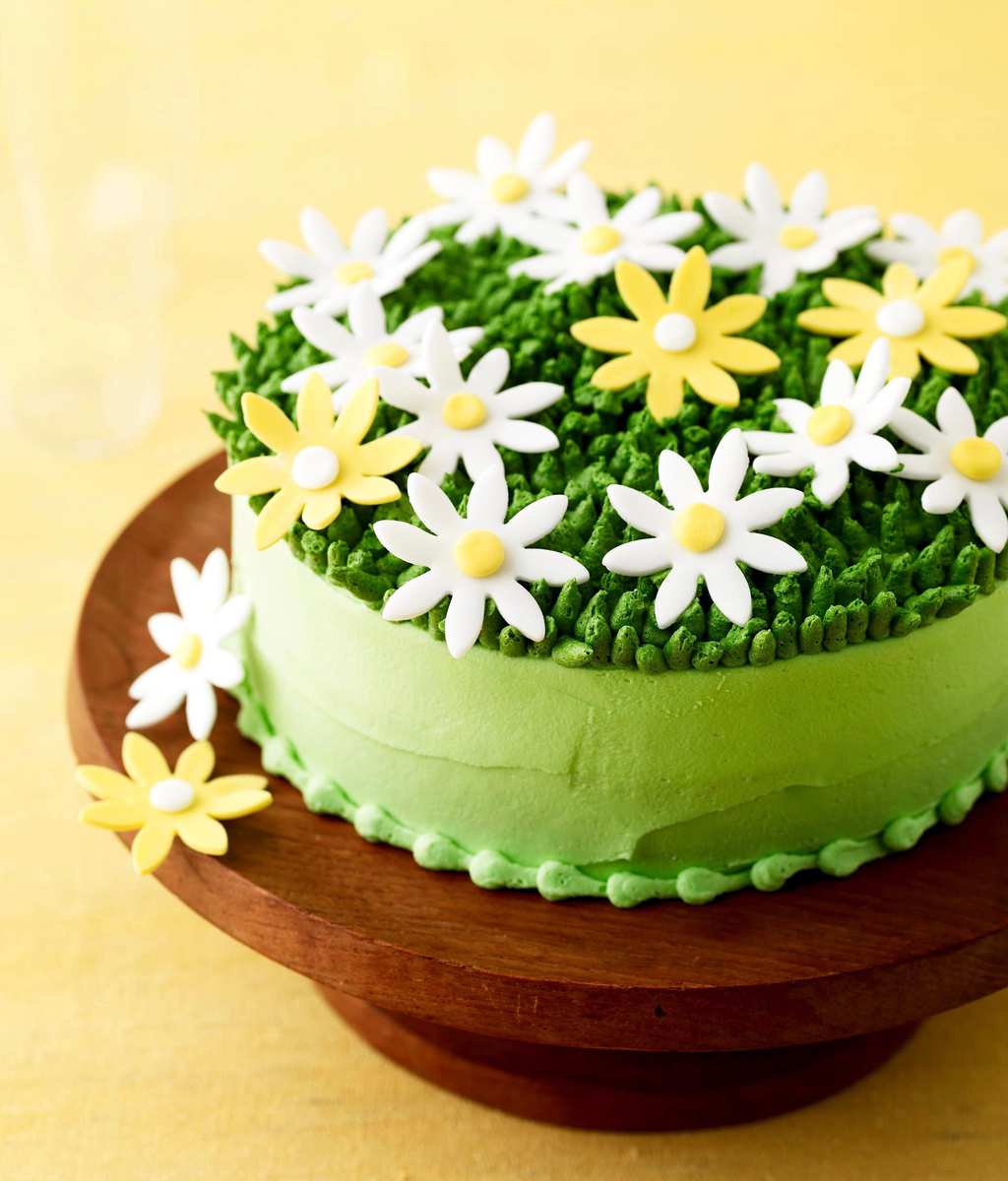 Green spring daisy cake on a wood pedistal