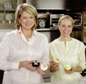 Martha Stewart and Tara Bench holding cupcakes in a kitchen