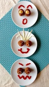 Three versions of meatball faces on white plates