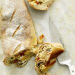 Alfredo Veggie Stromboli slices with knife on parchment