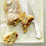 Alfredo Veggie Stromboli with slices and a knife on parchment