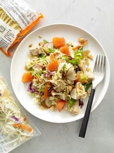 Crunchy Chicken Salad on white plate surrounded by ingredients