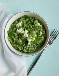 Spring Green Risotto in bowl on light blue surface