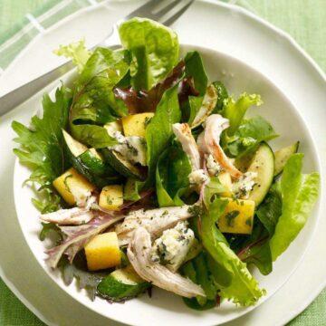 Warm Polenta Zucchini Salad in white bowl on green surface