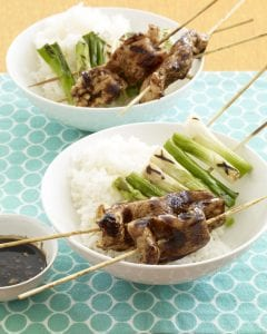 Two bowls of white rice and teriyaki chicken kabobs
